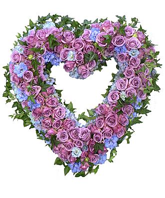 Blomsterhjärta av lila rosor och blå hortensia dekorerat med murgröna hos Bellis blomsterhandel.