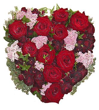 Blomsterhjärta i röda och rosa toner med bl.a. röda rosor, kvistrosor, murgröna hos Bellis blomsterhandel.