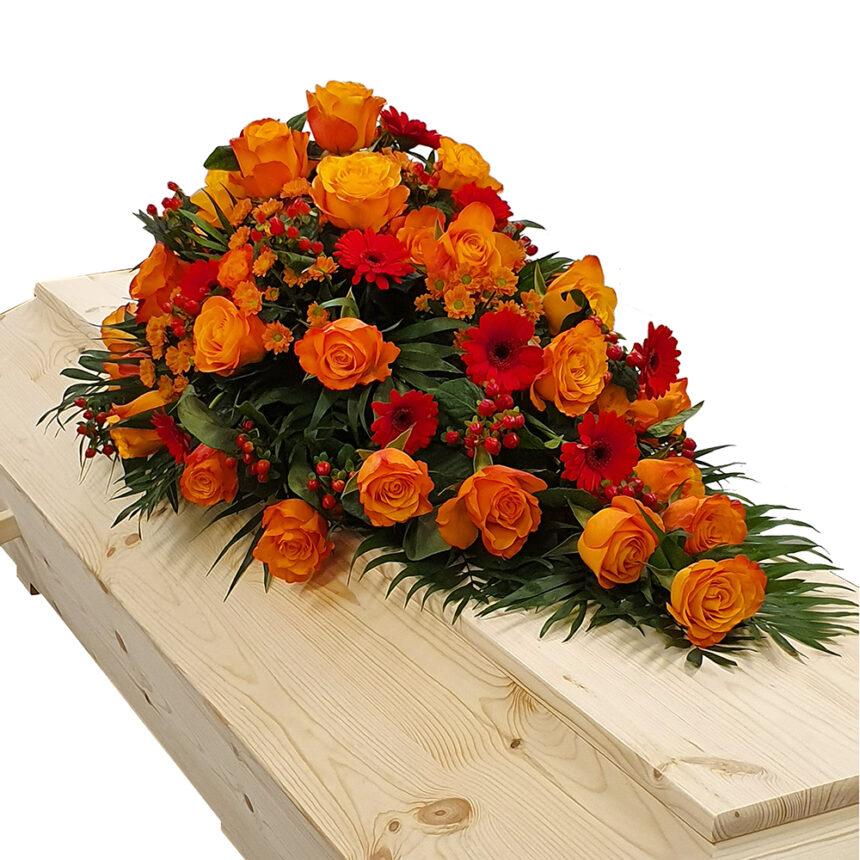 Kistdekoration i varma toner med bla rosor, santini, hypericum och germini hos Bellis blomsterhandel.