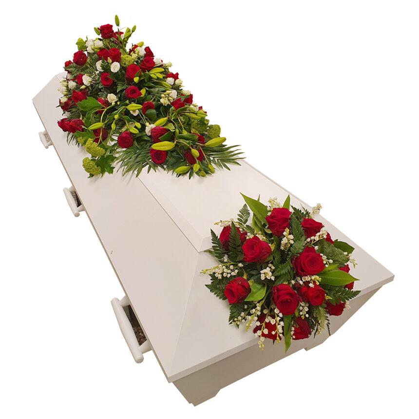 Kistdekoration med fotbukett med röda rosor, vit prärieklocka, limefärgade viburnum, liljor och liljekonvalj hos Bellis blomsterhandel.