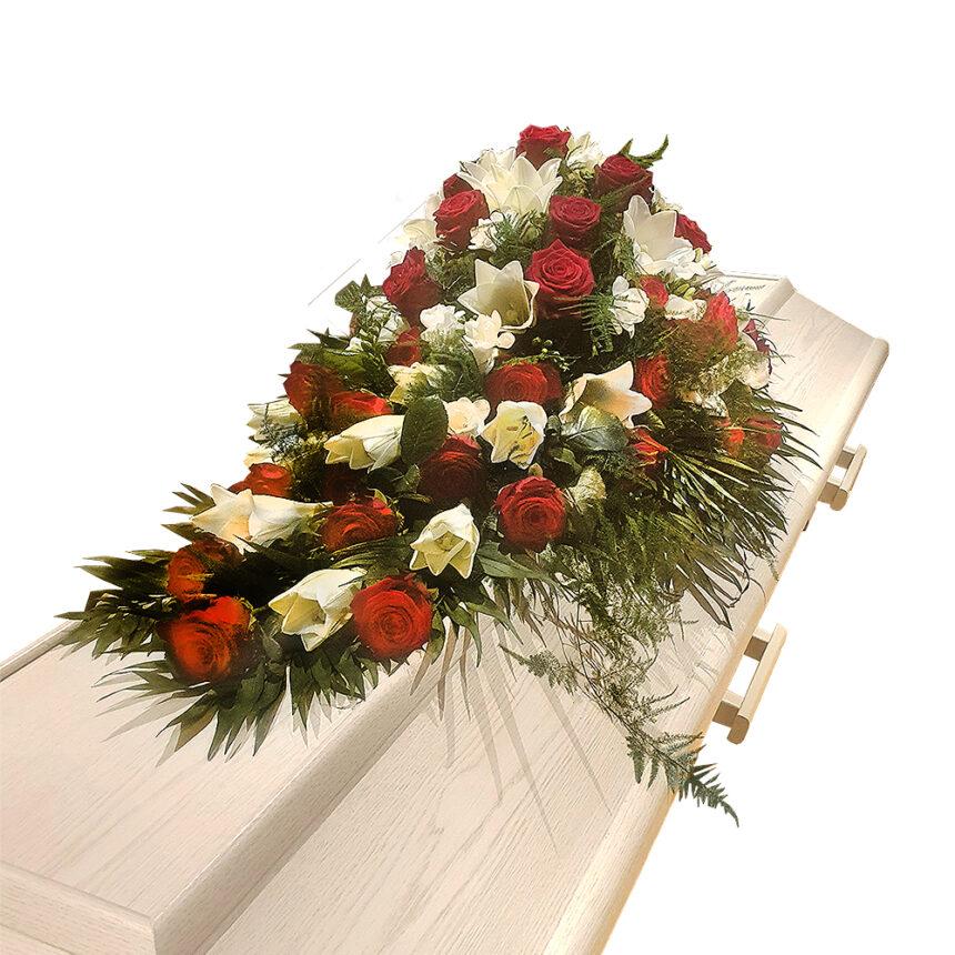 Traditionell kistdekoration med b.la. röda rosor och vita liljor hos Bellis blomsterhandel.