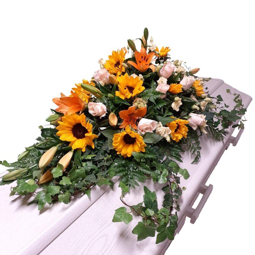 Kistdekoration av säsongens blommor innehållande solros hos Bellis blomsterhandel.
