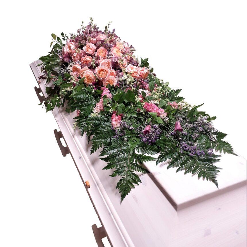Kistdekoration med lantlig prägel innehållande bl.a. rosor, delfinium, limonium (rispar) hos Bellis blomsterhandel.