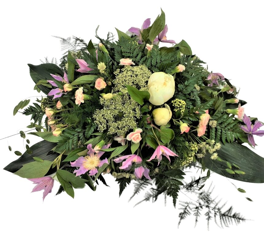 Låg begravningsdekoration i ljusa färger med bl.a. pion, elegansnejlika, kvistros, klematis hos Bellis blomsterhandel.