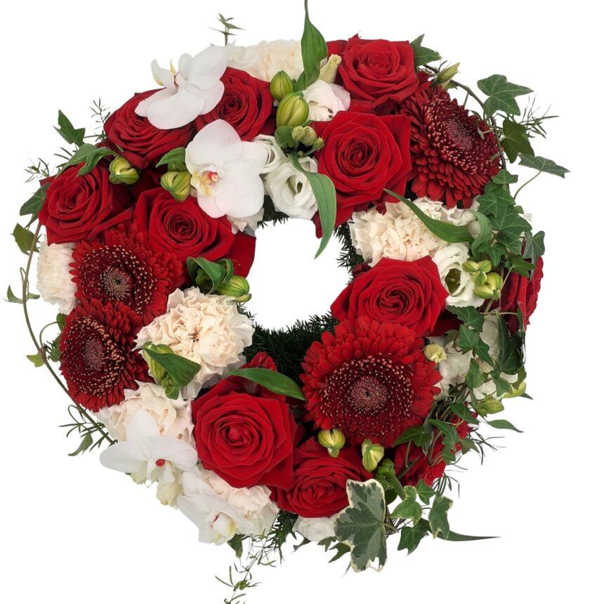 Begravningskrans i rött och vitt hos Bellis blomsterhandel.