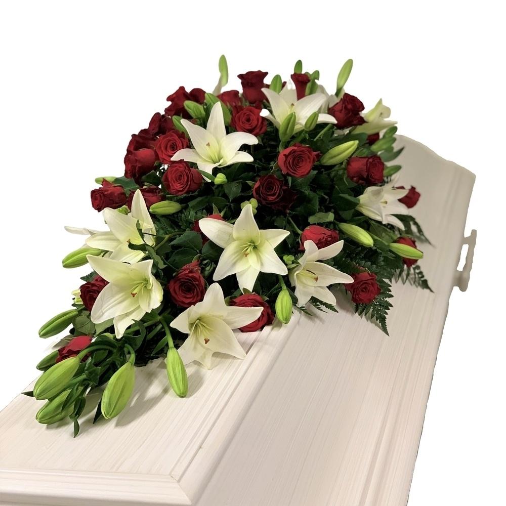 Kistdekoration innehållande bl.a. röda rosor och vita liljor hos Bellis blomsterhandel.