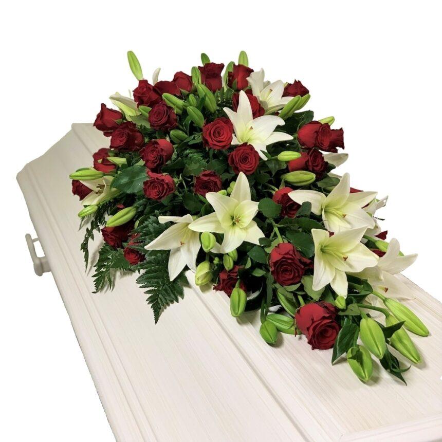 Klassisk kistdekoration med röda rosor och vita liljor hos Bellis Blomsterhandel