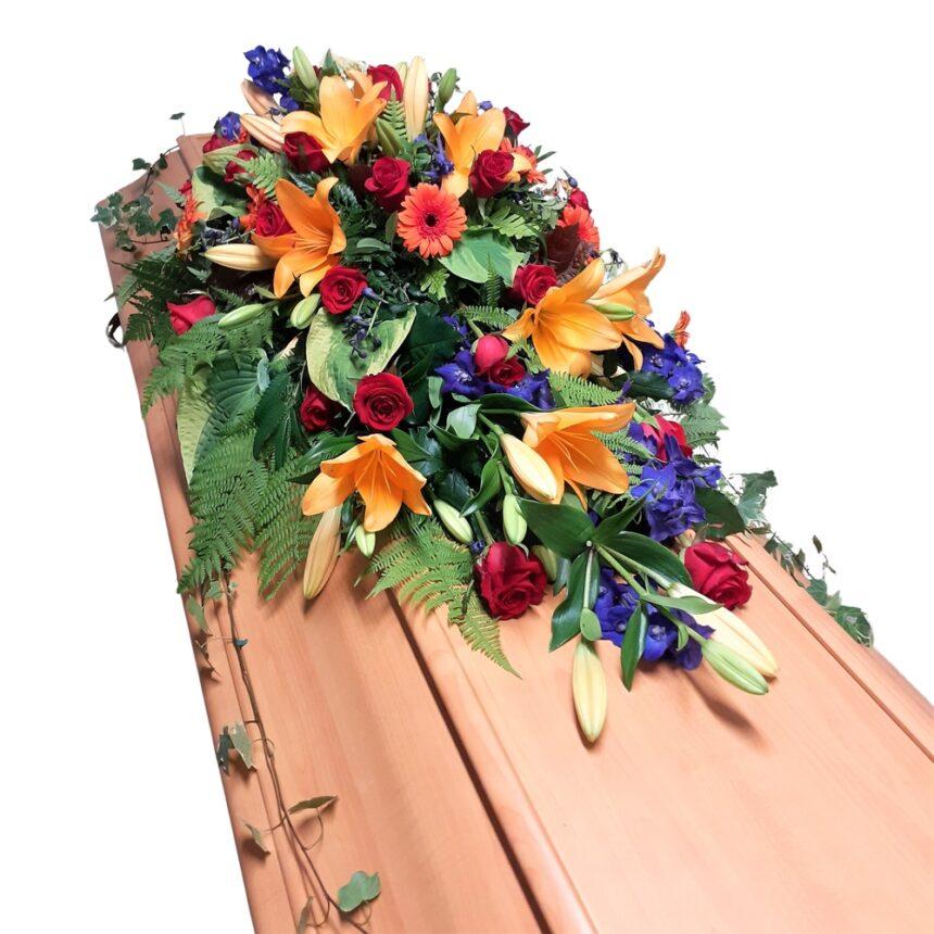 Kistdekoration i praktfulla färger innehållandes rosor, germini, lilja m.m. hos Bellis blomsterhandel.